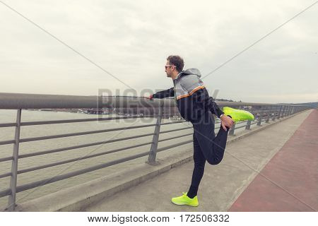 Urban jogger stretching / exercising on a big bridge.