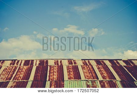 Old rusted and weathered steel quonset hut roof against a blue sky with fluff clouds vintage tone