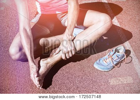 Female athlete with foot pain on running track on sunny day