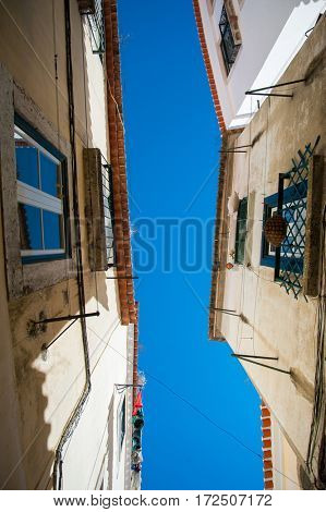 Street in Portugal. Old building with red tile roof in Lisbon, low angle view