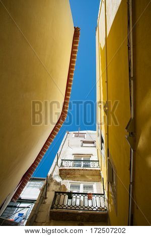 Street in Portugal. Old building with yellow walls in Lisbon, low angle view