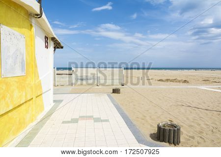 RIMINI,ITALY-APRIL 17,2015:white fence and yellow bar on the beach in Rimini-Italy-during a sunny day