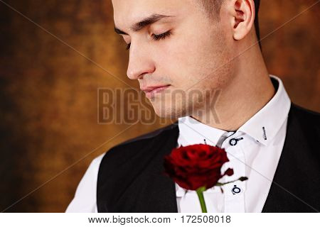A man holding a rose with eyes closed