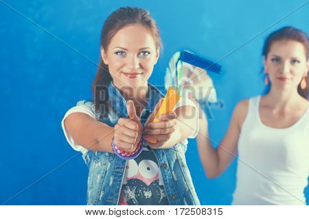 Two Beautiful young woman doing wall painting