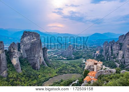 View of rock formations of the Meteora with Monastery of Roussanou and St. Nicholas Anapausas after sunset. Meteora Plain of Thessaly Greece Europe