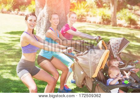 Women exercising with baby stroller in park