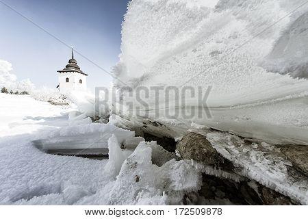 Ice floe on frozen lake Liptovska Mara. Tower of church on backround