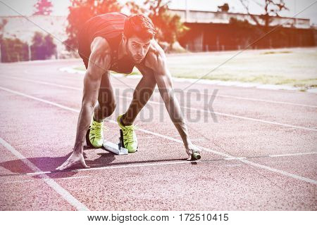 Athlete ready to start relay race on running track