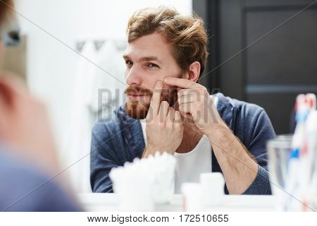 Young man squeezing pimple on his cheek in front of mirror