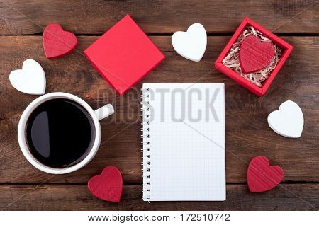 Coffee cup wooden hearts gift box with Valentine heart, open blank notebook on old background. Valentines day background. Writing romantic letters. Top view