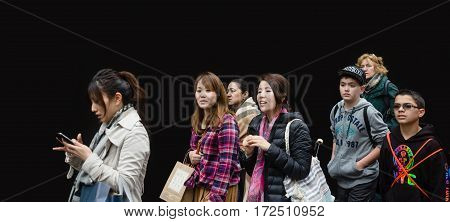 NEW YORK USA - May 03 2016: A group of young people of different nationalities the boys and girls go about their business against the black wall in Manhattan NYC