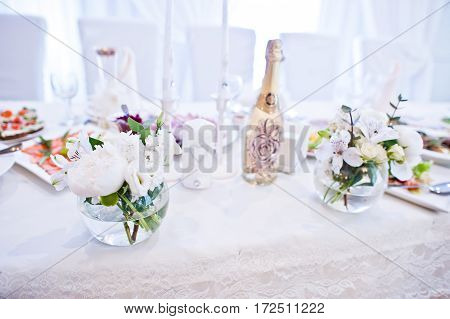 Champagne With Candles And Flowers Decor On Table Of Newlyweds At Wedding Hall.