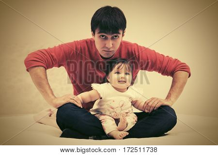 Father and baby girl sitting on blanket at home