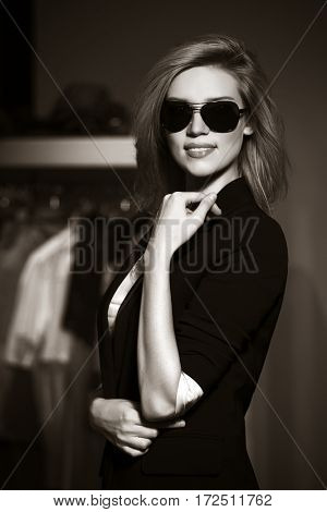 Young blond woman in sunglasses in the mall. Stylish fashion model
