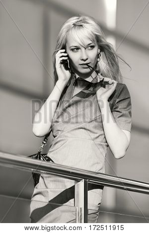 Young blond business woman calling on mobile phone. Stylish fashion model outdoor