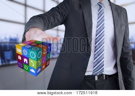 Businessman pointing at cube with his finger against room covered with windows
