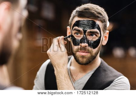 Client of parlor with professional moisturizing mask on face
