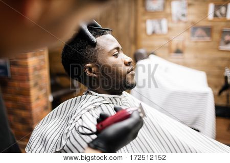 Man wrapped in napkin sitting in armchair in barbershop