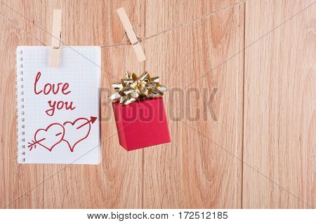 Valentines background with copy space. Note with words Love you and gift box hanging on the clothesline