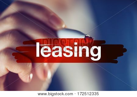 Leasing business concept - businesswoman highlighting word with red marker pen