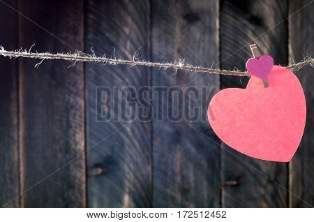 Valentines background with copy space. Hanging paper heart with clothespin. Rustic style