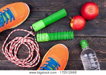 Sports equipment. Sport shoes skipping rope apple and bottle of water on the old wooden background. Sport and healthy life concept. Top view