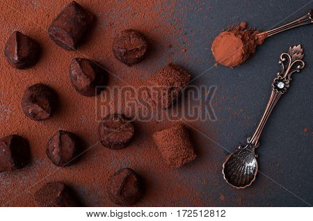 Chocolate truffles candy cocoa powder and dessert spoons on a dark background. Top view