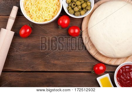 Ingredients for pizza. Dough rolling pin cherry tomatoes olive oil olives tomato sauce and cheese on a wooden table. Cooking pizza. View from above