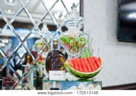 Cut Watermelon And Macarons With Bootle Of Cognac On Wedding Reception.
