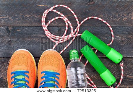 Sport shoes skipping rope and bottle of water on the old wooden background. Sports equipment. Sport and healthy life concept. Top view