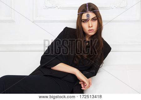 Young woman in black jacket sitting on sofa at home. Stylish fashion model indoors