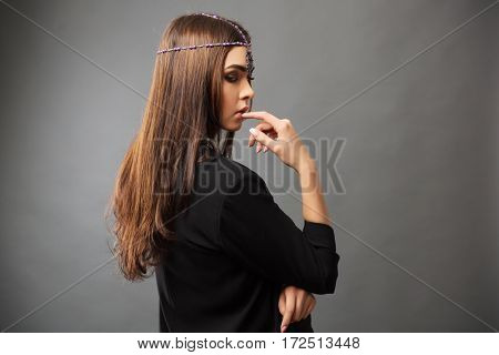 Sad young woman in black jacket on dark background. Stylish fashion model indoors