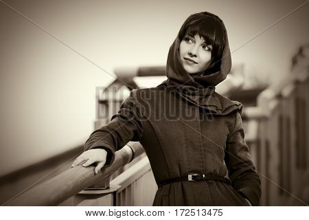 Happy young woman in classic coat walking on city street. Stylish fashion model outdoor