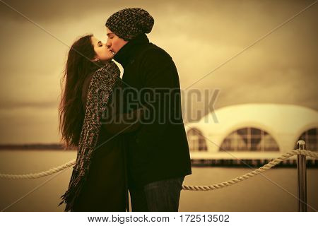 Happy young couple in love kissing on the pier. Stylish fashion model outdoor