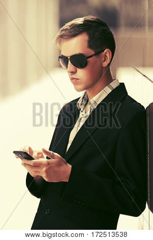 Young business man in sunglasses using smart phone on city street. Stylish fashion model outdoor