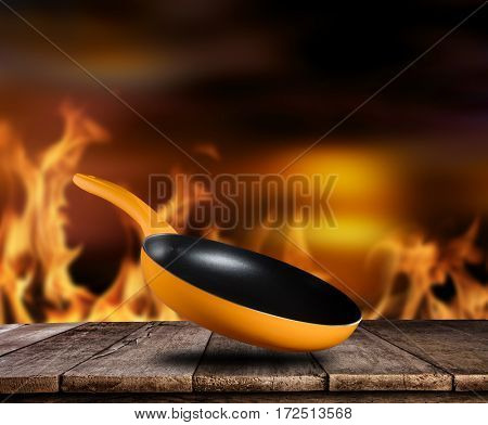 Empty pan with flames on background, ideal for product placement. Fire on background