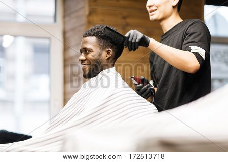 Barber taking care of his client hair