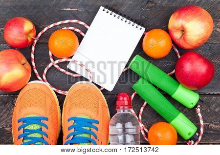 Sports shoes jumping rope apple citrus bottle of water and open blank notebook. Sport equipment. Healthy lifestyle food vegetarian and sport concept. Top view