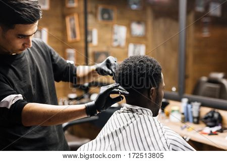 Barbers cutting client hair with scissors