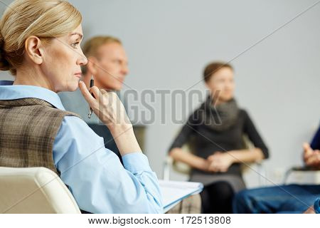 Pensive mature psychotherapist with pen on background of her patients