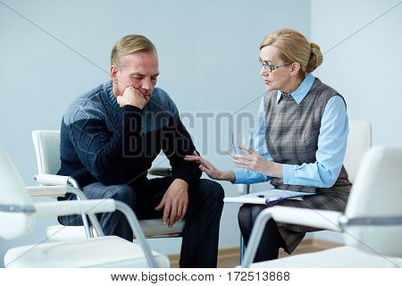 Mature psychiatrist offering glass of water to despaired man