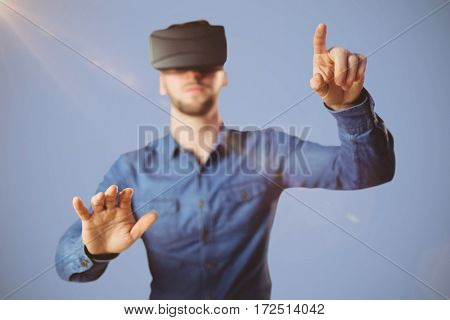 Man using a virtual reality device against grey background