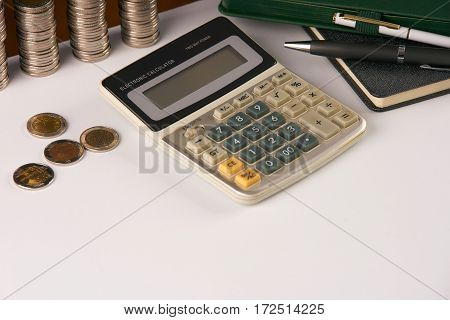 Home savings budget concept.notepad pen calculator and coins on white office desk table