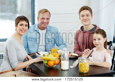 Healthy family members having breakfast by kitchen table