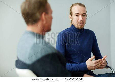 Young man sharing his trouble with psychotherapist