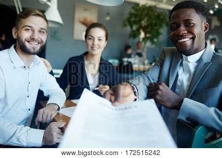 Young staff giving document to new partner to read and sign