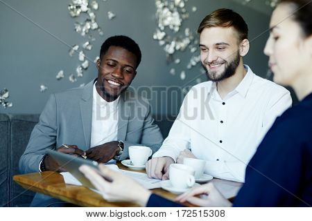 Happy designers listening to report of colleague at meeting