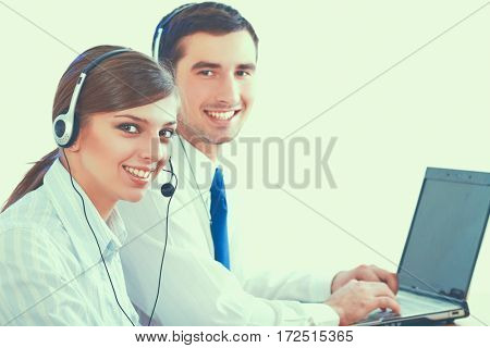 Young business woman and handsome businessman in headsets using laptops while working in office