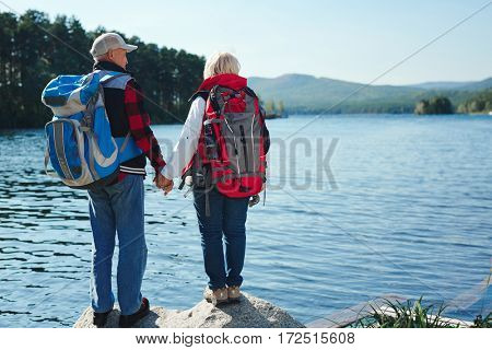 Senior tourists enjoying peace by lake