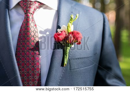 Young stylish groom in blue jacket, white shirt and red tie with boutonniere.
